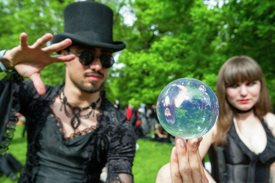 A man and a woman looking into a mirrorball attend the traditional park picnic on the first day of the annual Wave-Gotik Treffen, or Wave and Goth Festival, on May 17, 2013 in Leipzig, Germany. The four-day festival, in which elaborate fashion is a must, brings together over 20,000 Wave, Goth and steam punk enthusiasts from all over the world for concerts, readings, films, a Middle Ages market and workshops. Photo: Marco Prosch, Getty Images / 2013 Getty Images