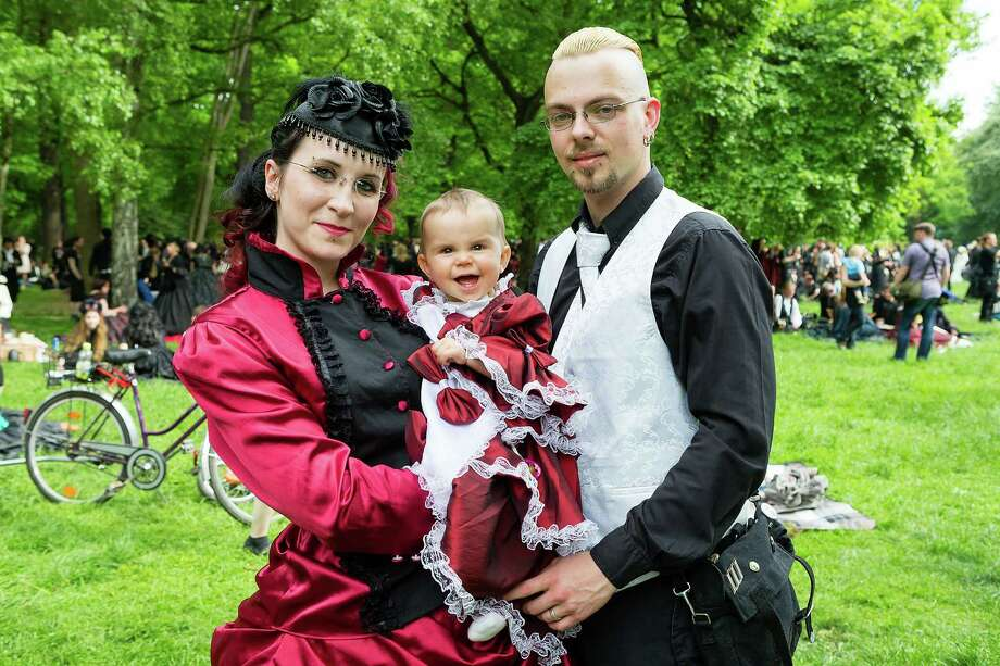 A young family dressed in Victrorian costumes pose for pictures during the traditional park picnic on the first day of the annual Wave-Gotik Treffen, or Wave and Goth Festival, on May 17, 2013 in Leipzig, Germany. The four-day festival, in which elaborate fashion is a must, brings together over 20,000 Wave, Goth and steam punk enthusiasts from all over the world for concerts, readings, films, a Middle Ages market and workshops. Photo: Marco Prosch, Getty Images / 2013 Getty Images