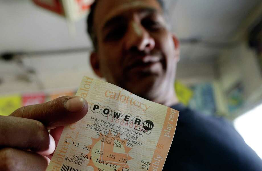 Joe Fajardo poses holding his Powerball lottery ticket after buying it at a store Saturday, May 18, 2013, in the Barrio Logan neighborhood of San Diego. With the majority of possible combinations of Powerball numbers in play, someone is almost sure to win the lottery game's highest jackpot on Saturday night, a windfall of hundreds of millions of dollars — and that's after taxes. (AP Photo/Gregory Bull) Photo: Gregory Bull