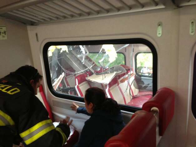 The first row of seats in the eastbound train, seen through the window, are crushed after Friday's Metro-North train collision in Bridgeport.