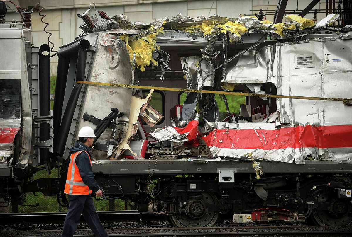 Metro North train cars heavily damaged in Friday's derailment are pulled from the scene after being hoisted back on to the tracks in Bridgeport. Conn. on Sunday, May 19, 2013.