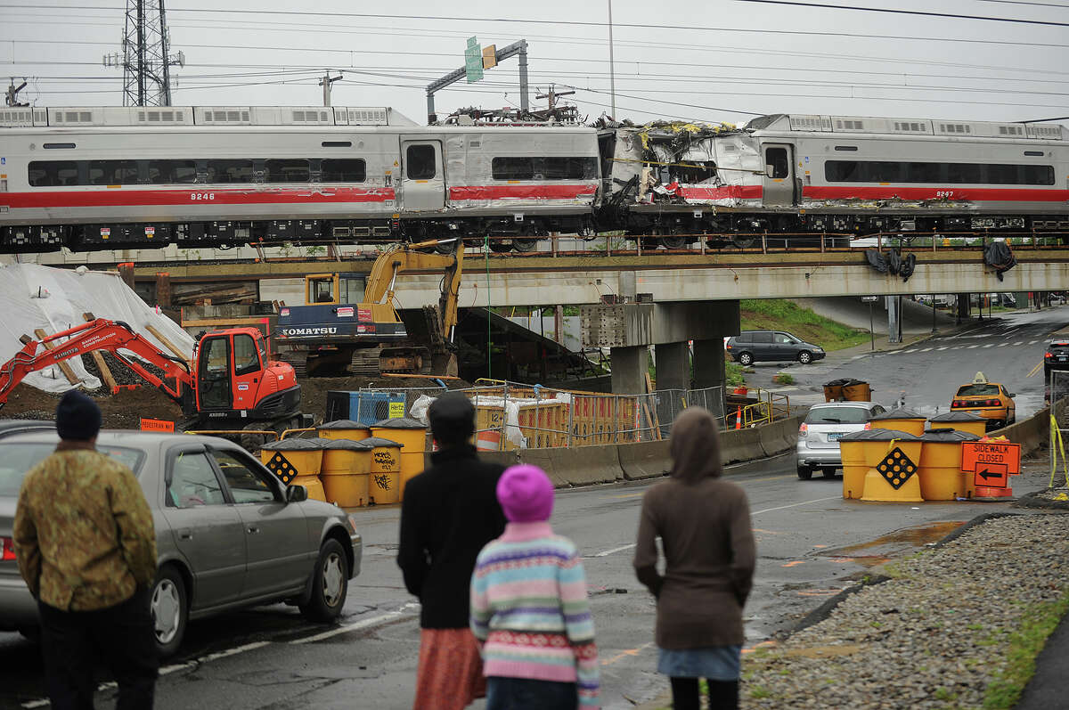 Metro North train cars heavily damaged in Friday's derailment cross Fairfield Avenue in Bridgeport, Conn. as they are pulled from the scene on Sunday, May 19, 2013.