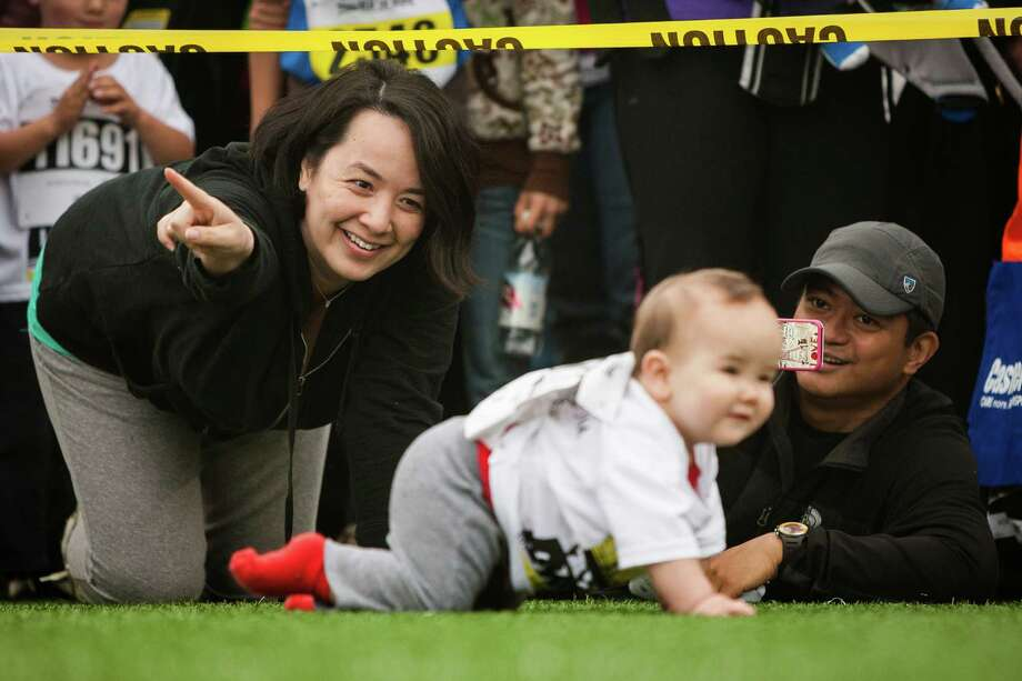 Parents attempt to point their babies in the right direction during the Diaper Derby following the 31st annual Nordstrom Beat the Bridge event Sunday, May 19, 2013, in Seattle. The fundraiser for JDRF is the largest charitable supporter of type 1 diabetes research. The event consists of an 8K run and wheelchair race, a 4-mile walk, a 1-mile fun run and the Diaper Derby for toddlers. Photo: JORDAN STEAD, SEATTLEPI.COM / SEATTLEPI.COM