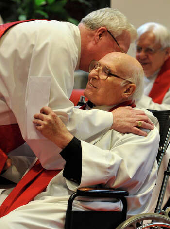 Deacon Paul Jennings, left, hugs Father Robert Hyl during Sunday mass at Church of the Holy Spirit in Stamford on May 19, 2013. Father Robert Hyl is celebrating his 50th year as a priest. Photo: Jason Rearick / Stamford Advocate