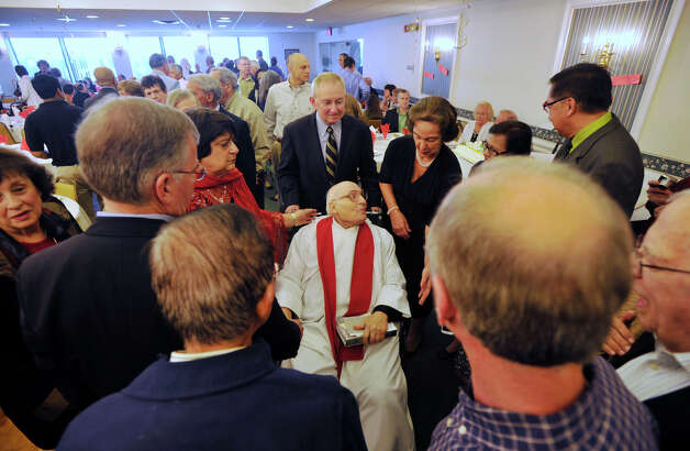 Well-wishers congratulate Father Robert Hyl, center, on his 50th year as a priest after Sunday mass at Church of the Holy Spirit in Stamford on May 19, 2013. Photo: Jason Rearick / Stamford Advocate