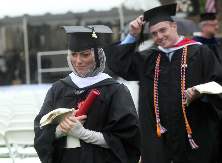 Julianne McGrath, of MA, tries to stay dry after receiving her diploma during Fairfield University's 63rd Commencement ceremony on the Fairfield, Conn. campus on Sunday, May 19, 2013. Photo: BK Angeletti, B.K. Angeletti / Connecticut Post freelance B.K. Angeletti