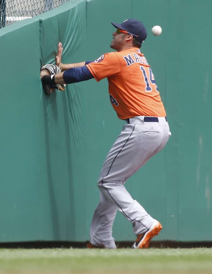 Astros left fielder J.D. Martinez looks for the wall as he chases after a foul ball