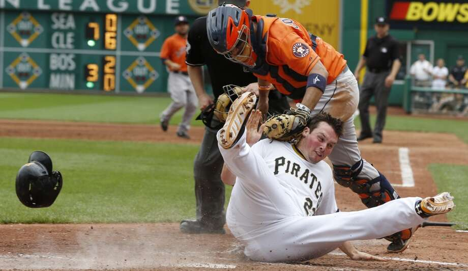 Travis Snider of the Pirates loses his helmet as he rolls into Astros catcher Jason Castro after being tagged out trying to score from second.
