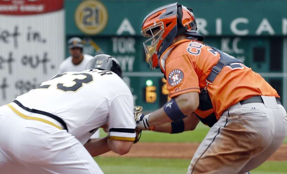 Travis Snider of the Pirates prepares to make contact with Astros catcher Jason Castro at home plate.
