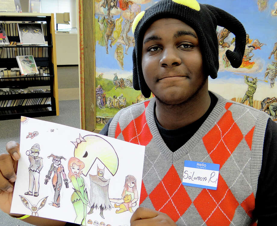 L. Solomon Ray, 15, shows an example of his hand-drawn comic illustrations at Westport Public Library's Comic-Con event Saturday. Photo: Mike Lauterborn / Westport News contributed