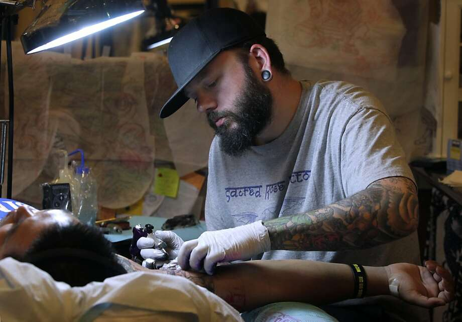 Zack Gaylord creates a tattoo for James Bunyajaroen at the Sacred Rose Tattoo parlor in Berkeley. The City Council is set to vote Tuesday on raising the registration fee for tattoo artists from $44 to $85. Photo: Paul Chinn, The Chronicle