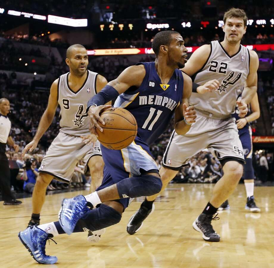 The Grizzlies' Mike Conley looks drives around the Spurs' Tony Parker and Tiago Splitter during first half action of the 2013 Western Conference Finals Sunday May 19, 2013 at the AT&T Center.