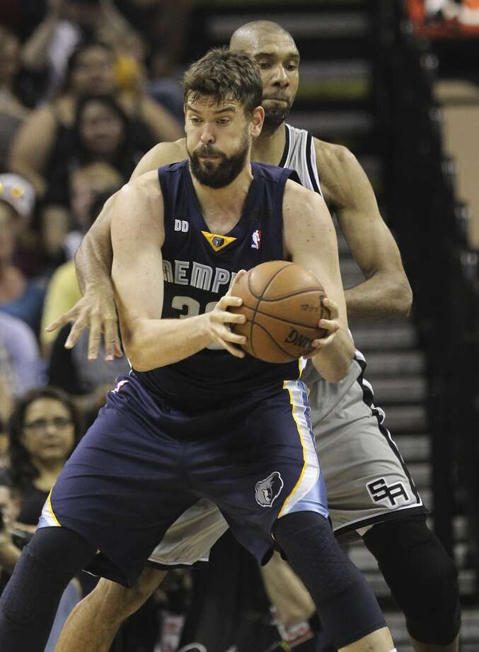 The Spurs' Tim Duncan (21) attempts to swat the ball away from the Grizzlies' Marc Gasol (33) in the first half of Game 1 of the 2013 Western Conference Finals at the AT&T Center on Sunday, May 19, 2013.