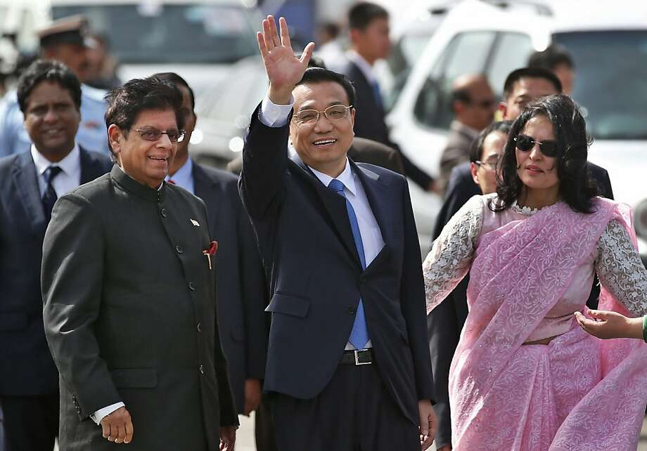 Arriving in New Delhi, Chinese Premier Li Keqiang waves as he is greeted by E. Ahamed (left), junior minister for external affairs, and a protocol officer. Photo: Saurabh Das, Associated Press