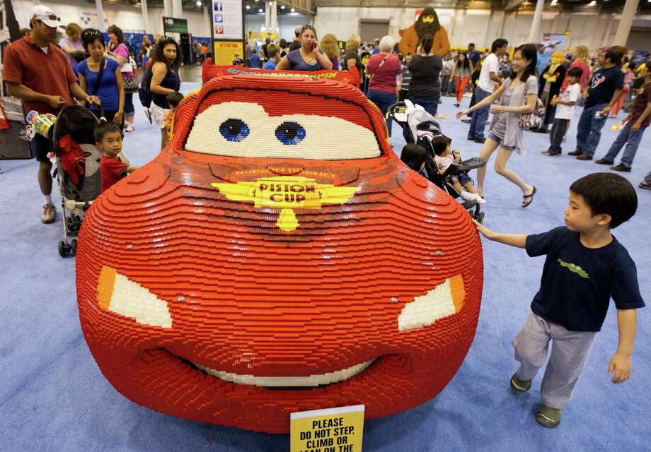 Aric Yang, 4, right, walks past a life size Lego model of Lightning McQueen from Pixar's movie Cars during Lego KidsFest national tour at Reliant Park on Sunday, May 19, 2013, in Houston. The three day event had three acres of hands-on educational fun for all ages including life-sized models made entirely from Lego bricks, construction zones for creative free build, and game arenas Photo: J. Patric Schneider, For The Chronicle / © 2013 Houston Chronicle