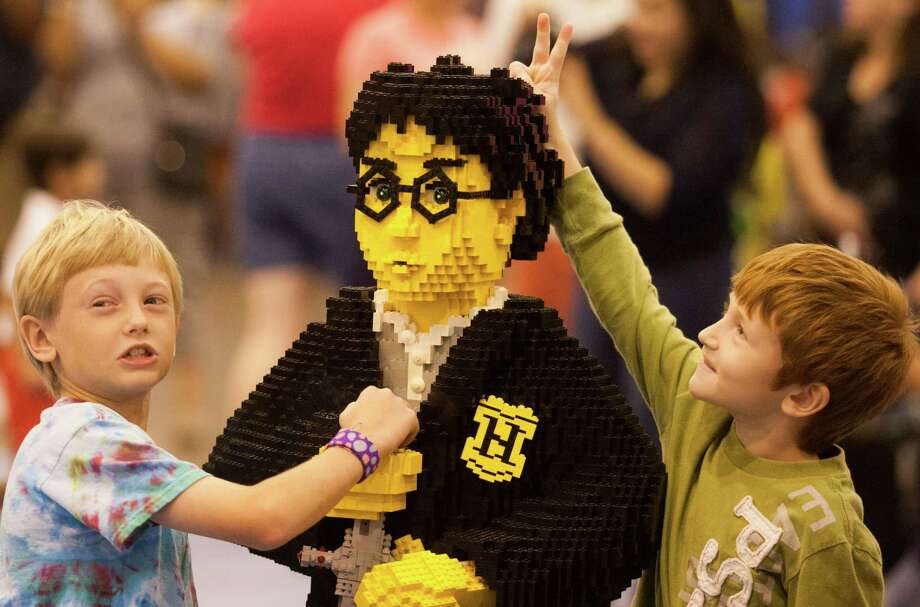 Easton Tucker, 9, left, and his brother Axel , 7, ham it up for their fathers picture with a life size Lego model of Harry Potter during Lego KidsFest national tour at Reliant Park on Sunday, May 19, 2013, in Houston. The three day event had three acres of hands-on educational fun for all ages including life-sized models made entirely from Lego bricks, construction zones for creative free build, and game arenas Photo: J. Patric Schneider, For The Chronicle / © 2013 Houston Chronicle