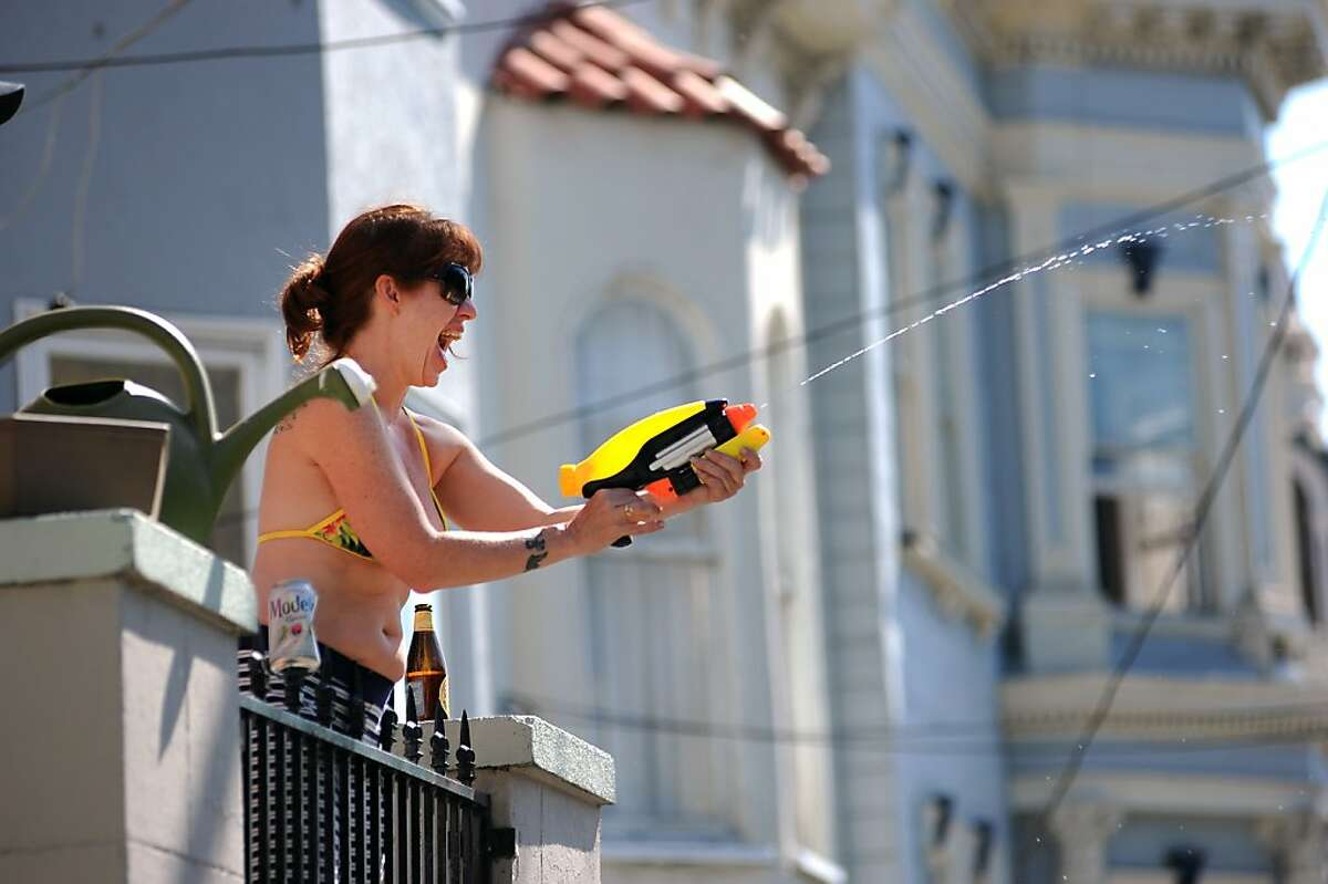 Jessica Brown sprays race participants with a squirt gun from her apartement on Hayes St. during the 102nd Bay to Breakers race in San Francisco, CA Sunday May 19th, 2013.