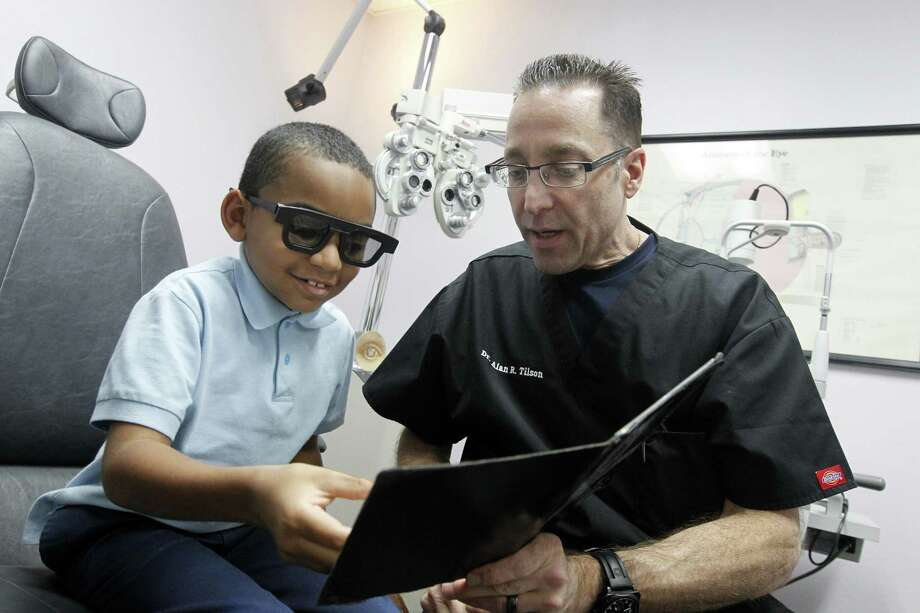 """Dr. Alan Tilson examines Bryant Newsome, 6, at Tilson EyeCare in Irving, which Tilson co-owns with his wife, an optician. Tilson says, """"I'll never fully retire ... but I want to be in a situation where if I didn't want to work, I don't have to."""" Photo: Photos By Kye R. Lee / McClatchy-Tribune News Service"""