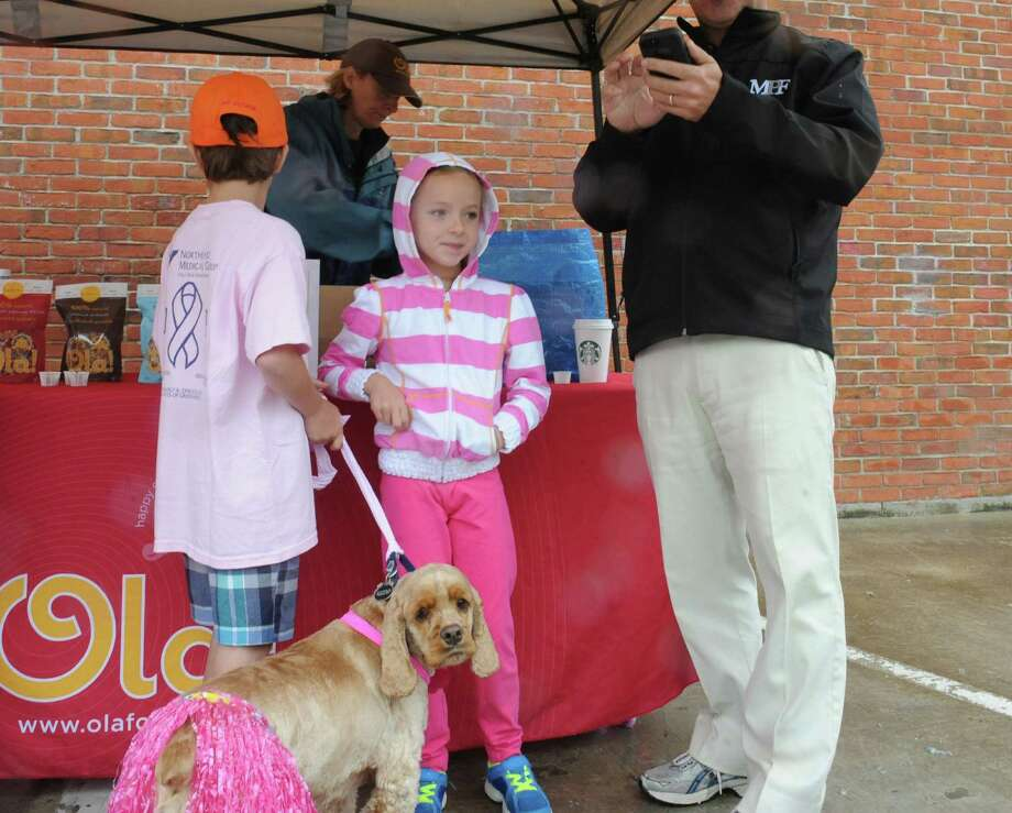 "Ryan Genovese, 9, Annie, their dog Cody and father David, registering at the Breast Cancer Alliance's ""Walk for Hope,"" at Richard's on Greenwich Avenue, in Greenwich, Sunday, May 19, 2013. The Alliance funds breast cancer research. Photo: Helen Neafsey / Greenwich Time"
