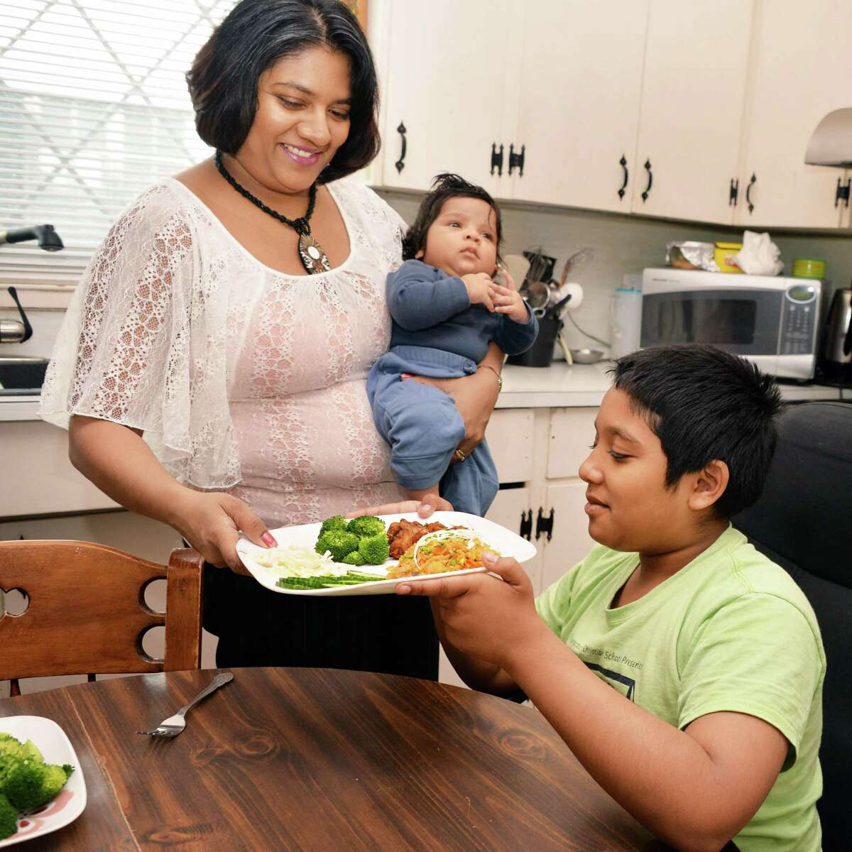 Veronica Baijnauth Gomes with sons, 3-month-old Baruch and Nathaniel, 11, in the kitchen of her Schenectady home Friday May 17, 2013. (John Carl D'Annibale / Times Union)