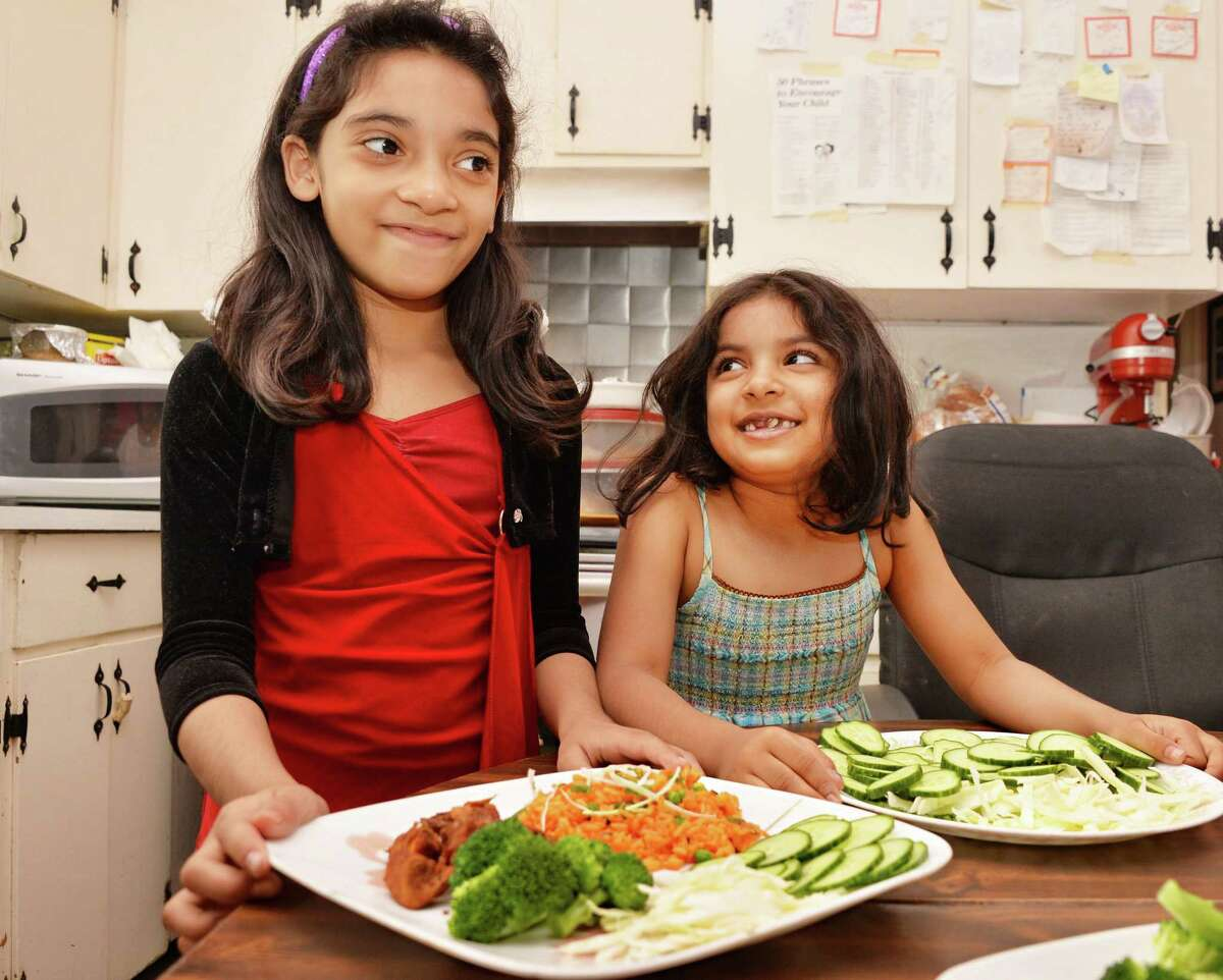 Veronica Baijnauth Gomes' daughters Gavriella, left, 8, and Adaniya, 6, help their mother serve lunch at their Schenectady home Friday May 17, 2013. (John Carl D'Annibale / Times Union)
