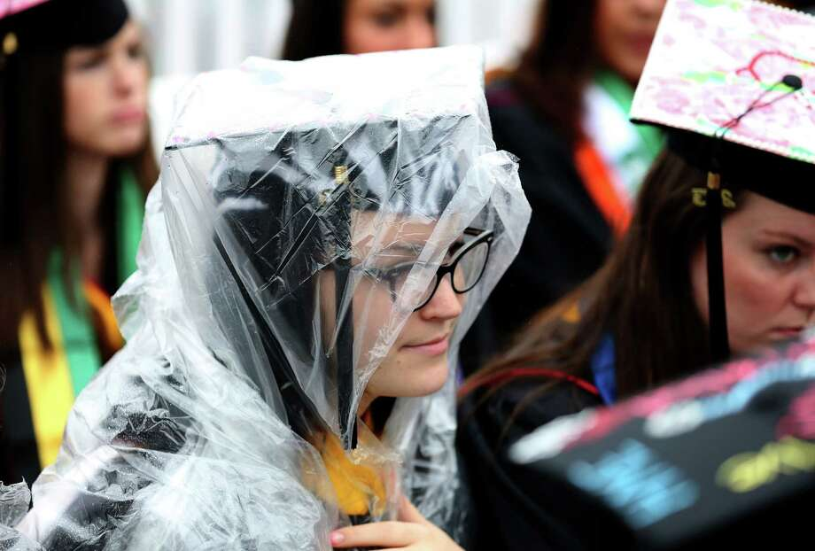 A Sacred Heart University graduate covers her head during the heavy rain at the commencement ceremony in Fairfield, Conn. on Sunday May 19, 2013. Photo: Mike Ross / Connecticut Post contributed