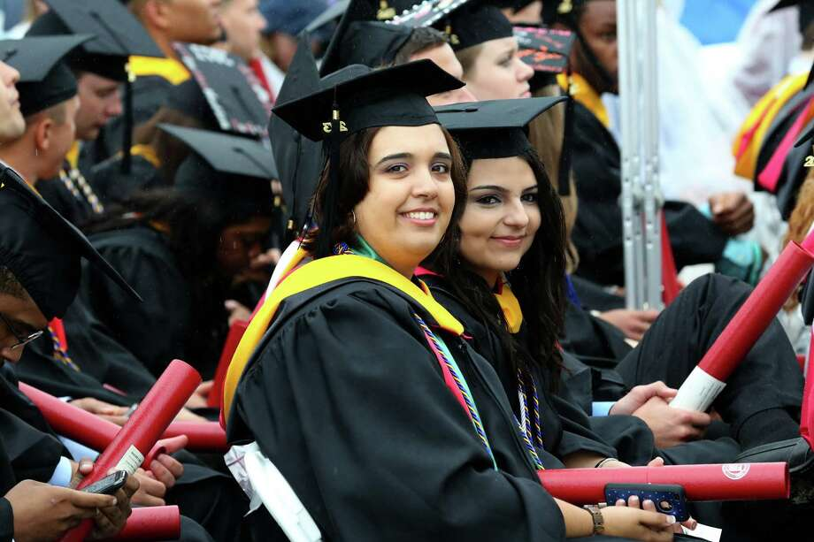 Sacred Heart University graduates Melissa Oliveira of Seymour and Jovana Ochua of Norwalk share a smile after receiving their diplomas during commencement exercises Sunday, May, 19, 2013. Photo: Mike Ross / Connecticut Post contributed