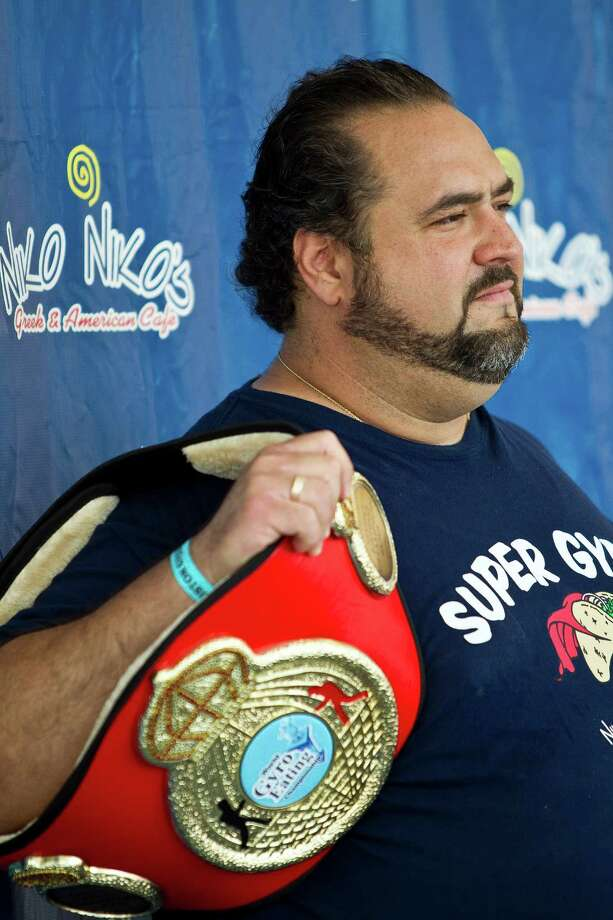 Dimitri Fetokakis, owner of Niko Niko's, holds the championship belt during the Sixth Annual Niko Niko's World Eating Championship during Houston Greekfest 2013, Sunday, May 19, 2013, at St. Basil's the Great Greek Orthodox Church in Houston. A new world record was set by Joey Chestnut eating 22 and a half half pound gyros with all the fixings. Photo: Nick De La Torre, Chronicle / © 2013 Houston Chronicle