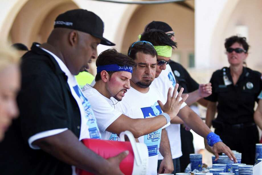 Juan Rodriguez, of Las Vegas, center, does karate moves to warm up before the Sixth Annual Niko Niko's World Eating Championship during Houston Greekfest 2013, Sunday, May 19, 2013, at St. Basil's the Great Greek Orthodox Church in Houston. A new world record was set by Joey Chestnut eating 22 and a half half pound gyros with all the fixings. Photo: Nick De La Torre, Chronicle / © 2013 Houston Chronicle