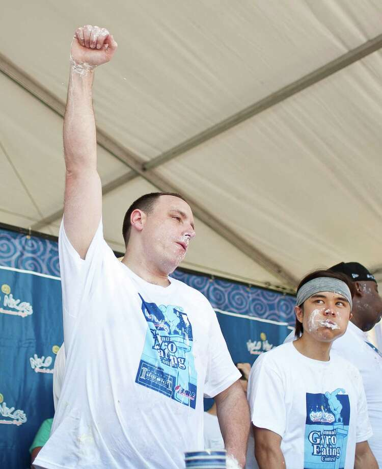 Joey Chestnut, of San Jose and the number one ranked competitive eater in the world, left, celebrates after winning the Sixth Annual Niko Niko's World Eating Championship during Houston Greekfest 2013, Sunday, May 19, 2013, at St. Basil's the Great Greek Orthodox Church in Houston. A new world record was set by Joey Chestnut eating 22 and a half half pound gyros with all the fixings. Photo: Nick De La Torre, Chronicle / © 2013 Houston Chronicle