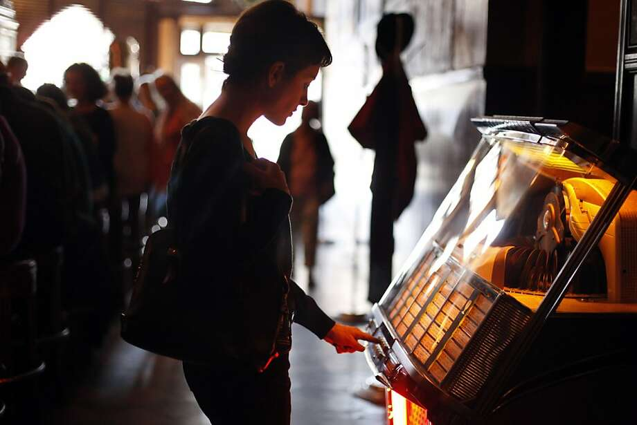 Nedelle Torrisi picks a song on the jukebox at Tosca Cafe on Sunday. Tosca Cafe in San Francisco, Calif., will be closing for a renovation and crowds gathered out the door to bid the San Francisco icon farewell on Sunday, May 19, 2013. Photo: Carlos Avila Gonzalez, The Chronicle
