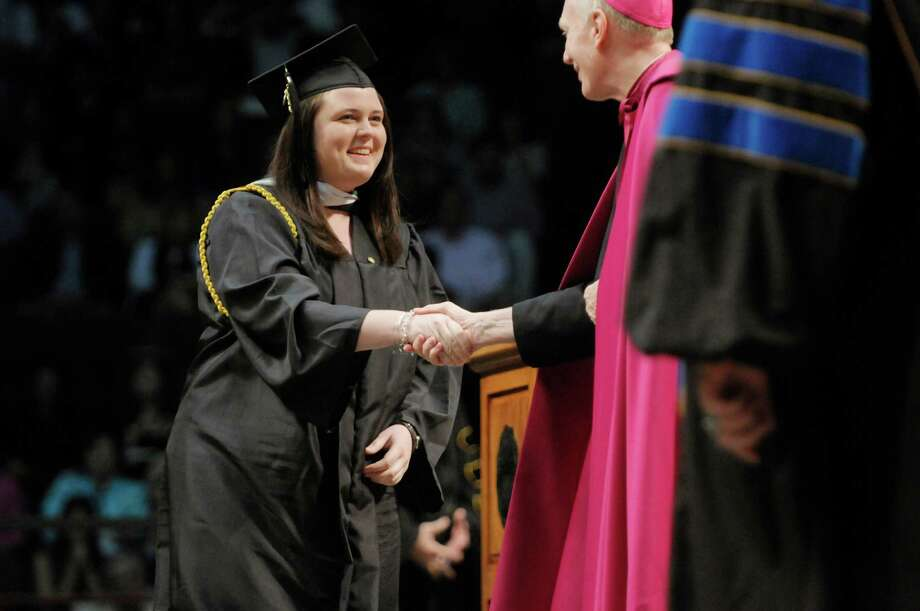 Graduate Christine Armstrong shakes hands with Albany Bishop Howard Hubbard as she walks across the stage to receive her diploma during the college commencement ceremony for Siena College at the Times Union Center on Sunday, May 19, 2013 in Albany, NY.  (Paul Buckowski / Times Union) Photo: Paul Buckowski