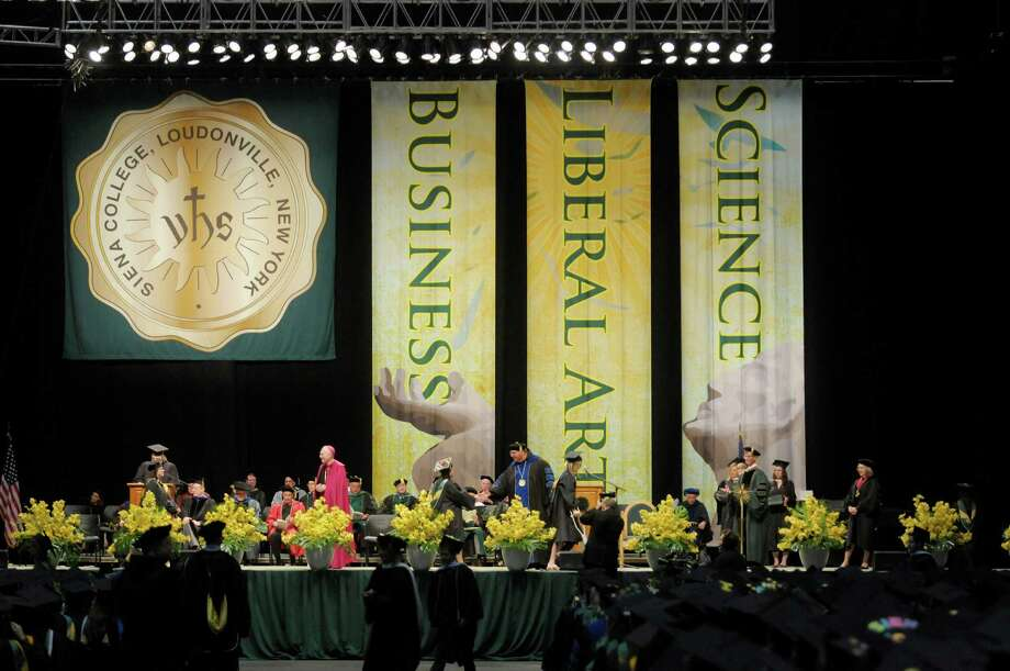 Graduates walk across the stage to receive their diplomas during the college commencement ceremony for Siena College at the Times Union Center on Sunday, May 19, 2013 in Albany, NY.  (Paul Buckowski / Times Union) Photo: Paul Buckowski
