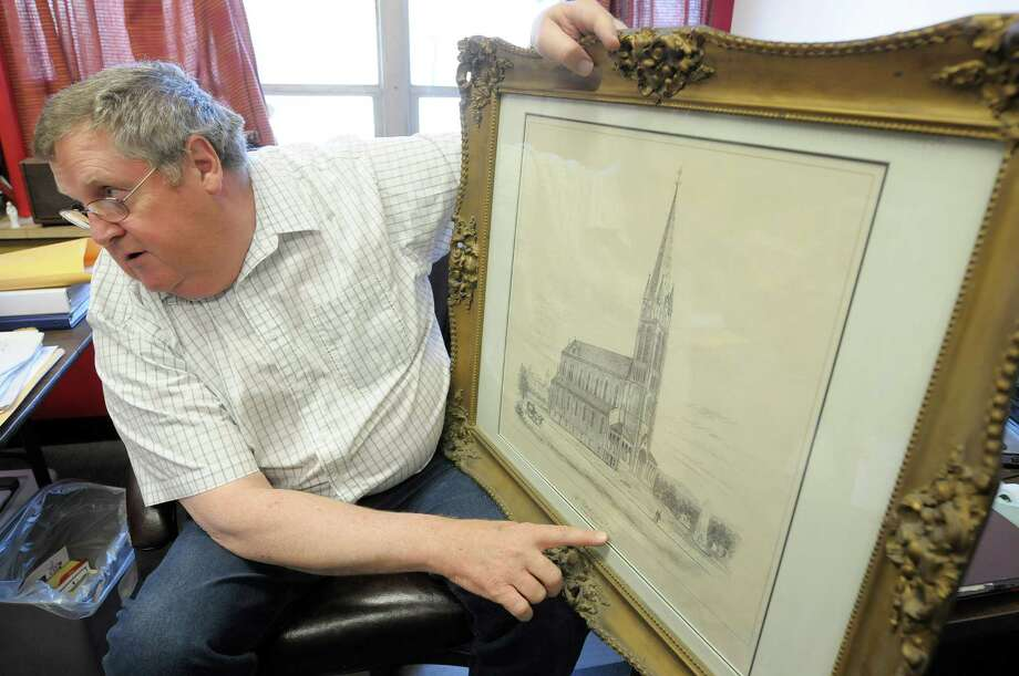 Immaculate Heart of Mary Church archivist, Tom Hanley shows an artist's drawing of St. Patrick's Church at his office on Thursday, May 16, 2013 in Watervliet, NY.  The drawing of the church shows a tall steeple that was never built because of costs according to Hanley.  (Paul Buckowski / Times Union) Photo: Paul Buckowski