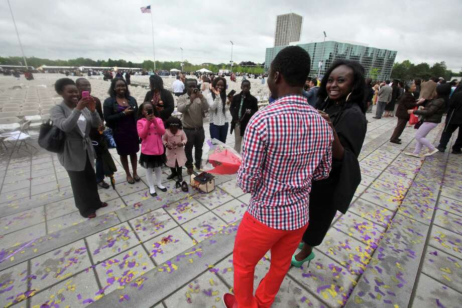 New graduate Afia Amonsah, far right, poses for pictures after the graduation commencement ceremonies at the University of Albany on Sunday, May 19, 2013. (Erin Pihlaja / Special to the Times Union)