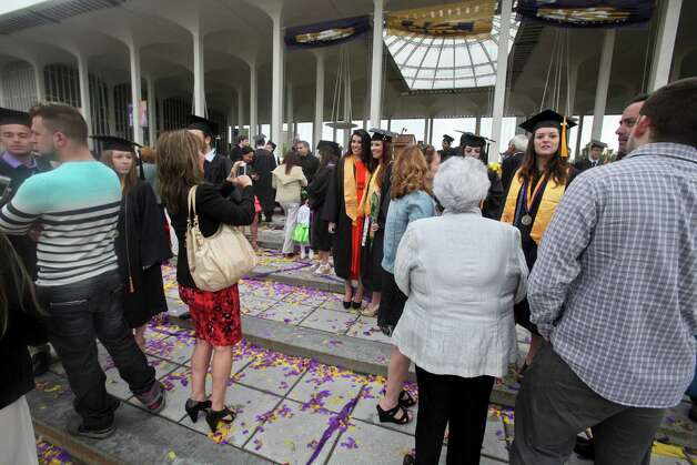 The podium is full of activity following the graduation commencement ceremonies at the University of Albany on Sunday, May 19, 2013. (Erin Pihlaja / Special to the Times Union)