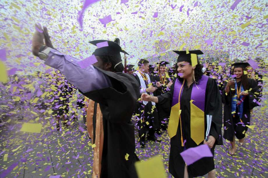 Mike Browne, left, and Nathalia Rivera, center, celebrate with other students at the graduation commencement ceremonies at the University of Albany on Sunday, May 19, 2013. (Erin Pihlaja / Special to the Times Union)