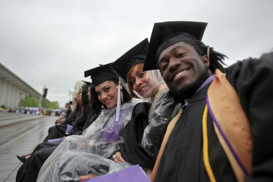 Nathalia Rivera, left, Cindy Ogando, center, and Mike Browne, right, at the graduation commencement ceremonies at the University of Albany on Sunday, May 19, 2013. (Erin Pihlaja / Special to the Times Union)