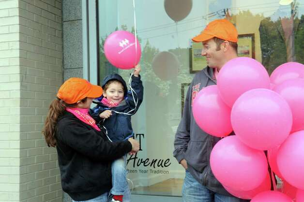 "Jenn Logan, Brewster, N.Y. holds her son Don, 3, while her husband, Don gives off balloons at the Breast Cancer Alliance's ""Walk for Hope,"" at Richard's on Greenwich Avenue, in Greenwich, Sunday, May 19, 2013. The Alliance funds breast cancer research. Photo: Helen Neafsey / Greenwich Time"