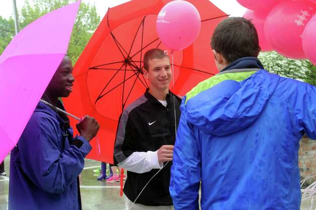 "From left: Lazare Zoungrana, 16, Ben Rogers, 16, and Alex Montinaro, 16, of Greenwich, giving out ballons at the Breast Cancer Alliance's ""Walk for Hope,"" at Richard's on Greenwich Avenue, in Greenwich, Sunday, May 19, 2013. The Alliance funds breast cancer research. Photo: Helen Neafsey / Greenwich Time"