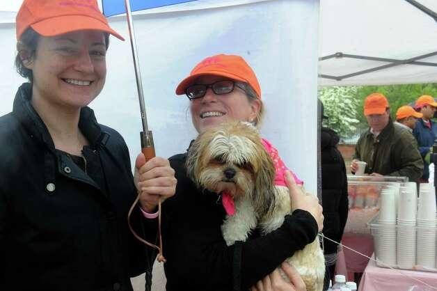 "Kerry Quin, left, and Abigail Clark, with her dog Jackson, 2, a Lhasa Apso, keep dry at the Breast Cancer Alliance's ""Walk for Hope,"" at Richard's on Greenwich Avenue, in Greenwich, Sunday, May 19, 2013. The Alliance funds breast cancer research. Photo: Helen Neafsey / Greenwich Time"