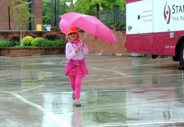 "Caitlin Maurer, 7, of Guilford, dancing in the rain at the Breast Cancer Alliance's ""Walk for Hope,"" at Richard's on Greenwich Avenue, in Greenwich, Sunday, May 19, 2013. The Alliance funds breast cancer research. Photo: Helen Neafsey / Greenwich Time"