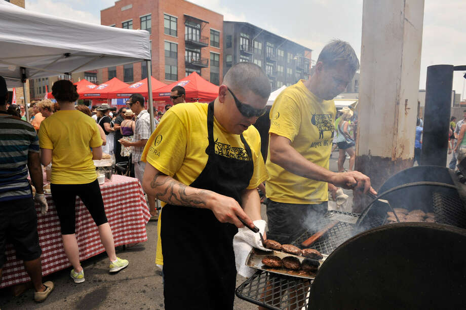 Jaime Gonzalez (left) and John Brand of Las Canarias cook burgers during the event. Sunday was the final day of the five-day Culinaria festival. Photo: Photos By Robin Jerstad / For The San Antonio Express-News