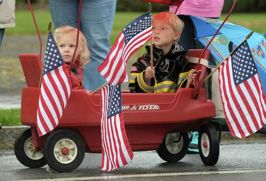 Natalie Dodge, 3, and her brother David Dodge, 5, watch for their father in the Altamont Memorial Day parade on Sunday, May 19, 2013 in Altamont, NY.  The children's father, David Dodge, is a volunteer member and past chief of the Guilderland Center Fire Department.  (Paul Buckowski / Times Union) Photo: Paul Buckowski