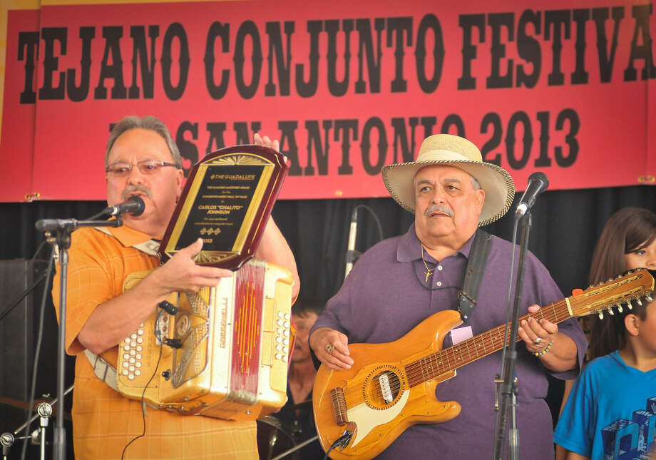 "Carlos ""Chalito"" Johnson (left) shows off the plaque he and his brother, Juan Johnson (right), were presented after they were announced as new members of the Conjunto Music Hall of Fame. Photo: Robin Jerstad / For The Express-News"