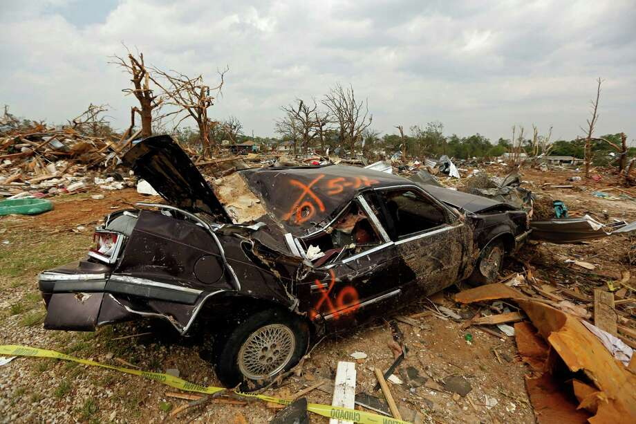 A smashed car sits in a debris field in the Rancho Brazos subdivision Sunday, May 19, 2013 in Granbury, Texas. Residents in the neighborhood continued cleanup of their damaged homes after a May 15 tornado wreaked havoc on the area, injuring dozens and killing six people. (AP Photo/The Dallas Morning News, G.J. McCarthy) Photo: G.J. McCarthy, MBR / The Dallas Morning News