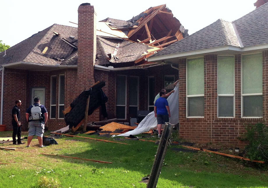 Residents of Edmond, Okla., survey storm damage from a tornado that hit their neighborhood Sunday, May 19, 2013. Forecasters had warned that the middle of the country would see severe weather throughout the weekend. (AP Photo/Sean Murphy) Photo: Sean Murphy, Associated Press / AP