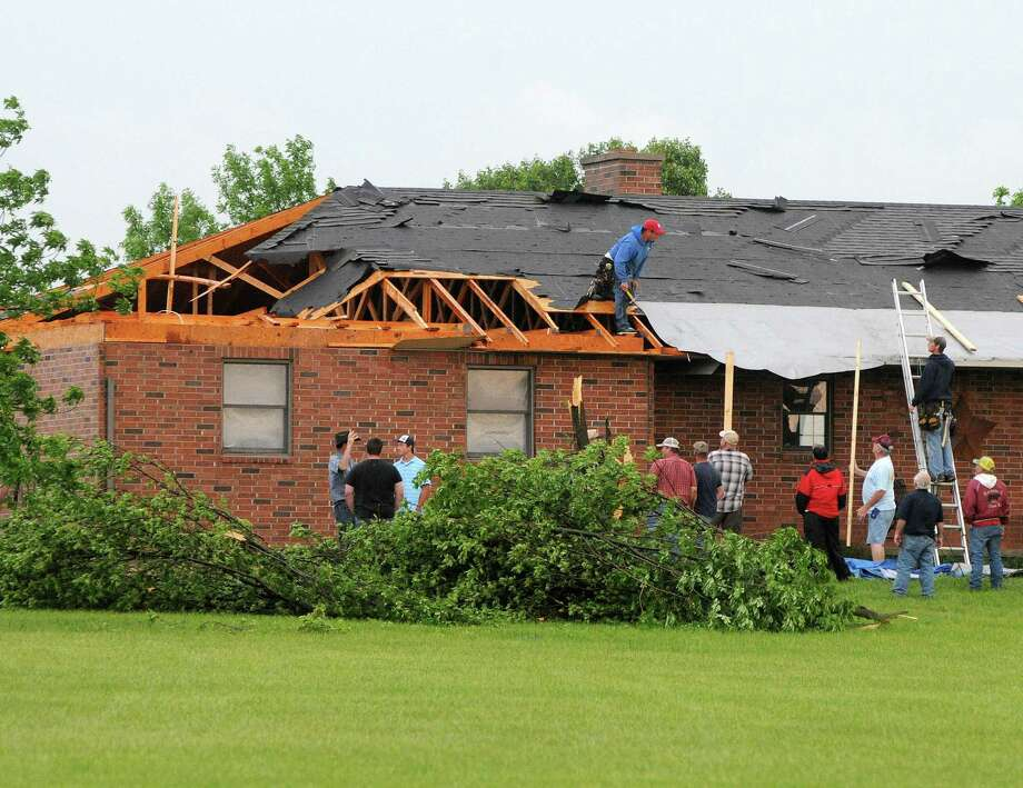 Friends and neighbors help out a resident in Lyon County just south of Emporia, Kan., Sunday evening, May 19, 2013 after an apparent tornado touched down. (AP Photo/Emporia Gazette, Matthew Fowler) Photo: Matthew Fowler, Associated Press / Emporia Gazette