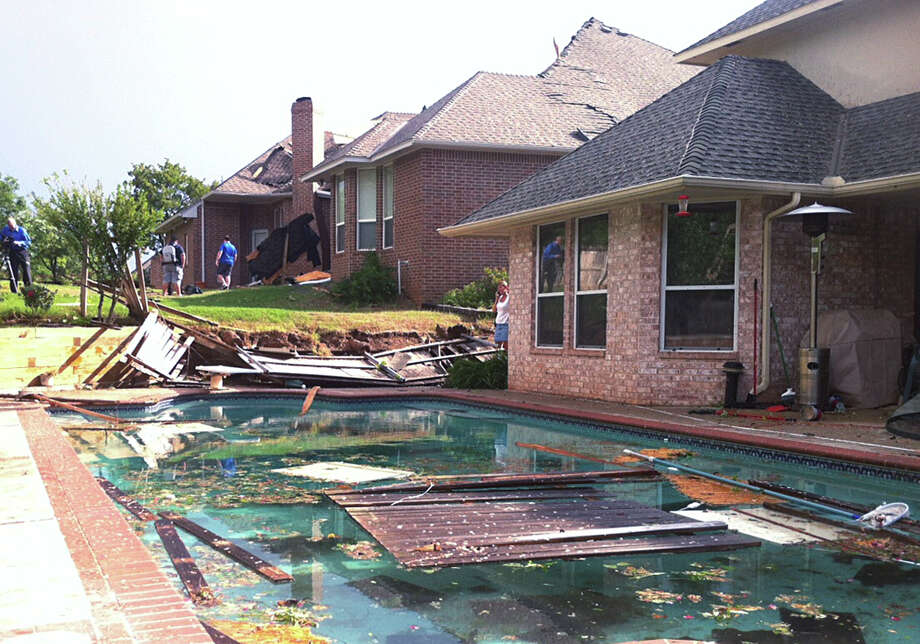 People survey damage from a tornado that hit Edmond, Okla., on Sunday, May 19, 2013. A powerful storm system rumbled through the Plains and upper Midwest on Sunday, spawning tornadoes that damaged roofs and structures near Oklahoma City and kicked up debris in Wichita, Kan. (AP Photo/Sean Murphy) Photo: Sean Murphy, Associated Press / AP