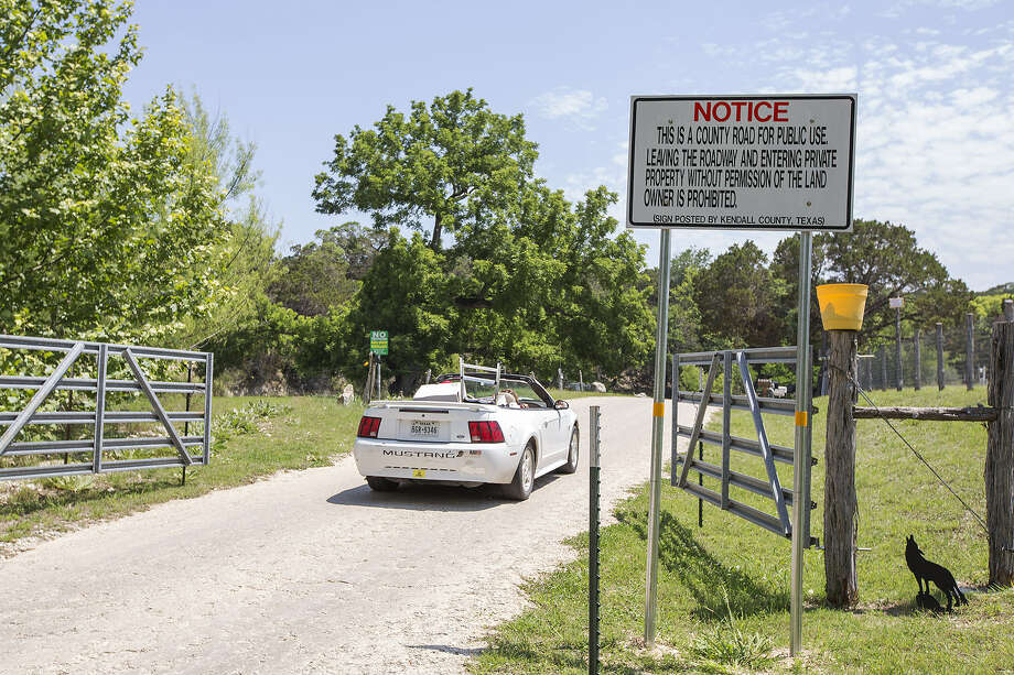 A driver passes a warning sign on Upper Cibolo Creek Road, which is the subject of a dispute involving residents and Kendall County. Photo: Michael Miller / For The San Antonio Express-News